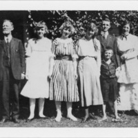 Two Men, Four Women and Boy Standing in Front of Greenery and Porch